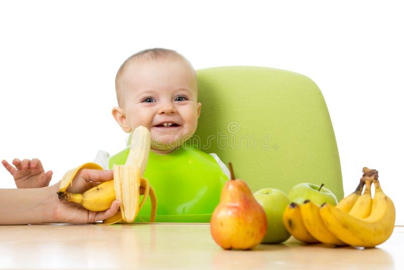 Bébé ayant une table complètement de nourriture saine Enfant en bas âge gai avec des pommes de fruits, bananes, poire D'isolement photographie stock libre de droits
