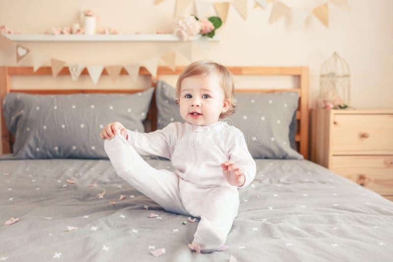 Bébé blond caucasien dans l'onesie blanc se reposant sur le lit dans la chambre à coucher photo stock
