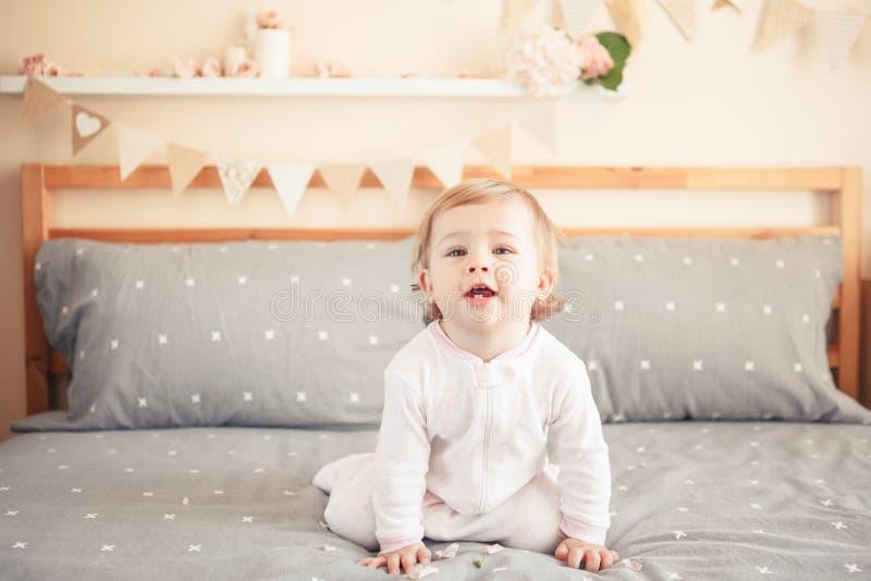 Bébé blond caucasien dans l'onesie blanc se reposant sur le lit dans la chambre à coucher photo libre de droits