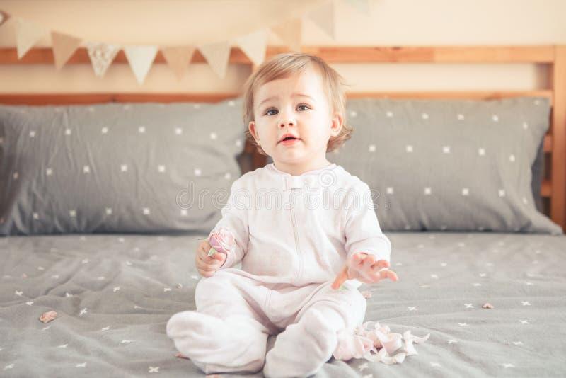 Bébé blond caucasien dans l'onesie blanc se reposant sur le lit dans la chambre à coucher photos stock