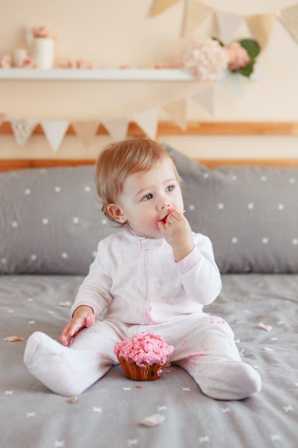 Bébé blond caucasien dans l'onesie blanc se reposant sur le lit dans la chambre à coucher image libre de droits