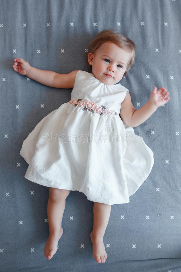 Bébé blond caucasien un an dans la robe blanche se trouvant sur le drap gris dans la chambre à coucher, vue à partir de dessus photo libre de droits