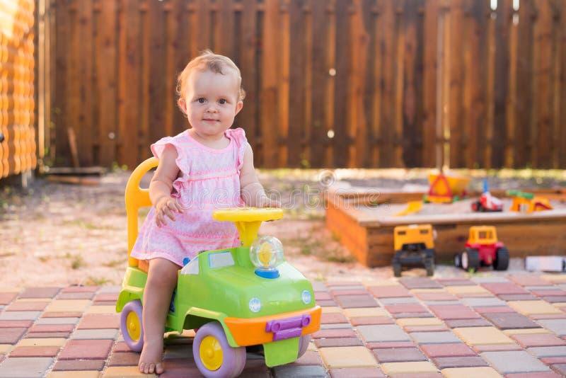 Bébé conduisant une voiture de jouet au terrain de jeu extérieur, fond d'été, l'espace de copie images stock