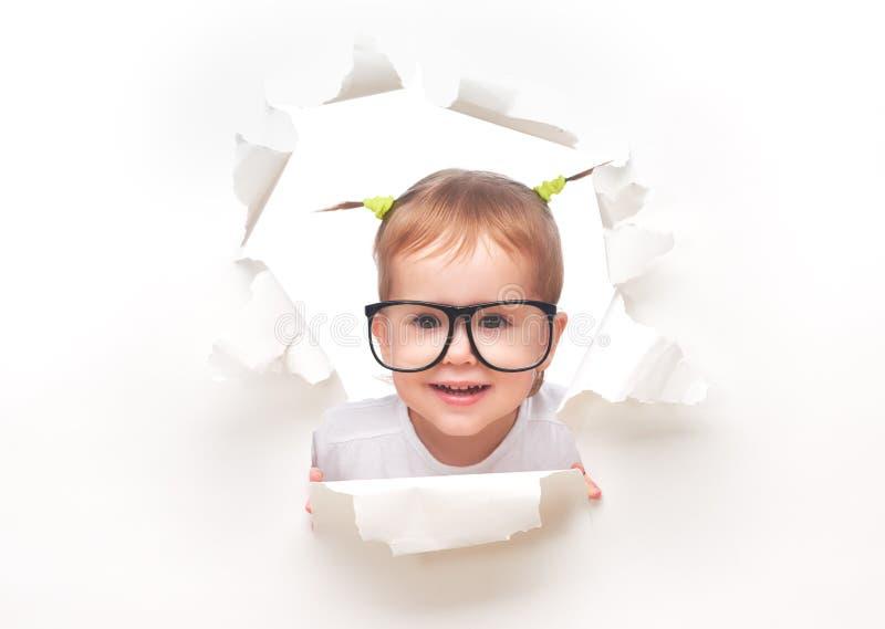 Bébé d'enfant avec les queues drôles avec des verres piaulant par un trou en livre blanc photos stock