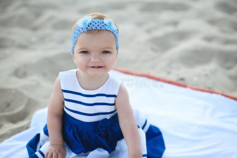 Bébé d'ute de ¡ de Ð dans la robe rayée intéressante et le bandeau bleu se reposant sur le sable souriant et lui montrant les pre photo libre de droits