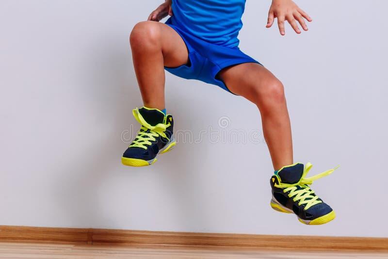 Bébé dans des espadrilles propres de basket-ball sautant haut sur le fond blanc image libre de droits