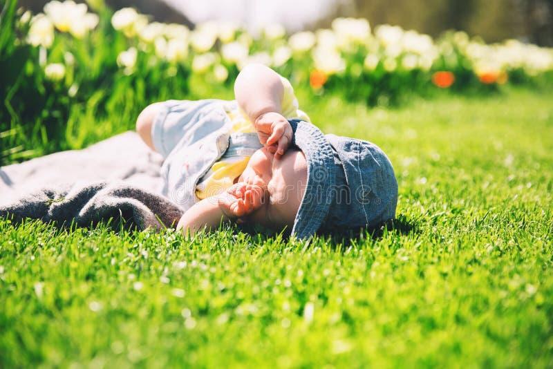 Bébé dans l'herbe verte du champ de tulipe au printemps photographie stock libre de droits