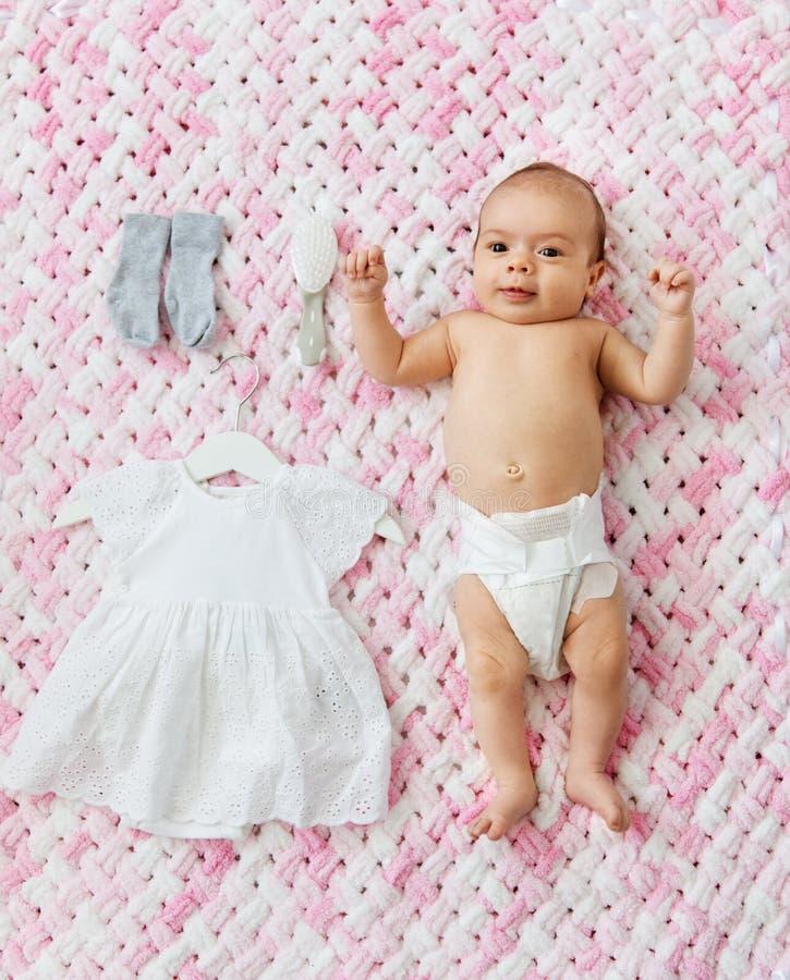 Bébé dans la couche-culotte se trouvant avec la robe sur la couverture photographie stock