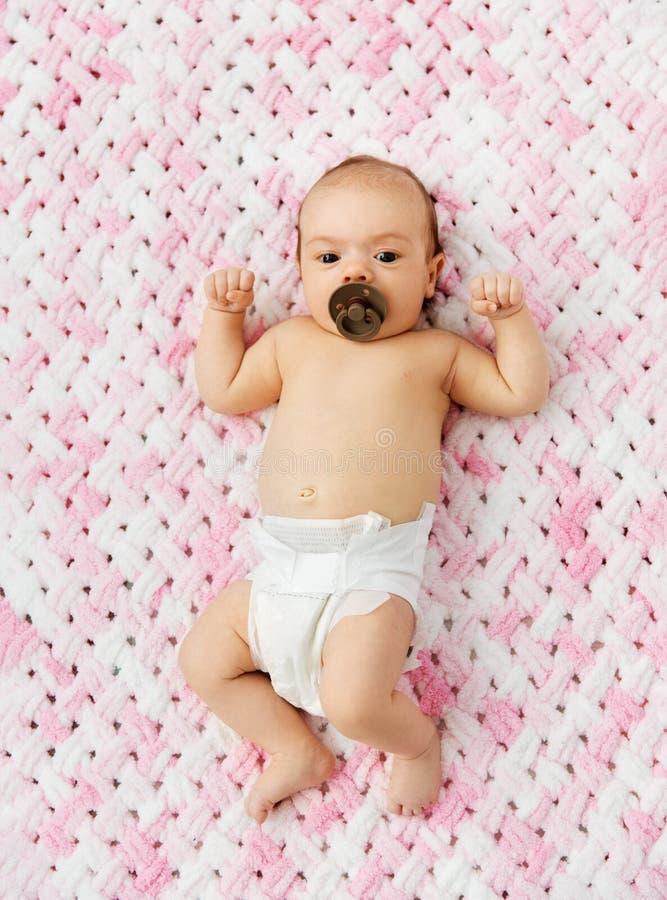 Bébé dans la couche-culotte se trouvant avec la tétine sur la couverture image libre de droits