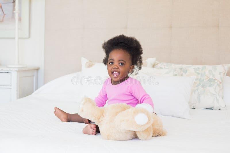 Bébé dans le babygro rose se reposant sur le lit photo libre de droits