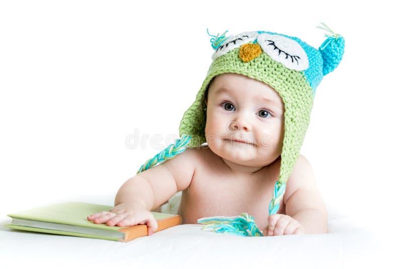 Bébé dans le hibou tricoté drôle de chapeau avec le livre images stock