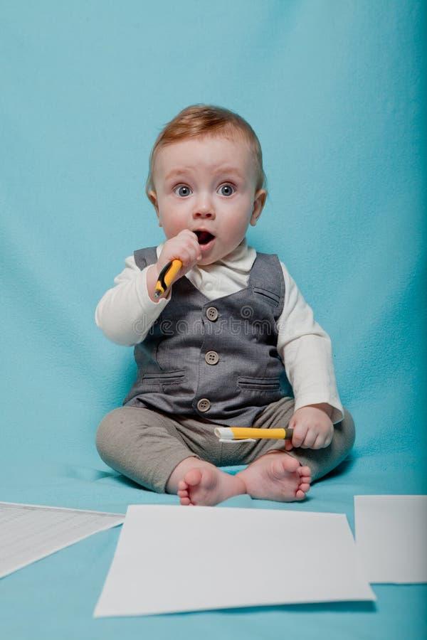 Bébé dans le style de bureau, stylo grisonnant de petit garçon sur le fond bleu photos libres de droits