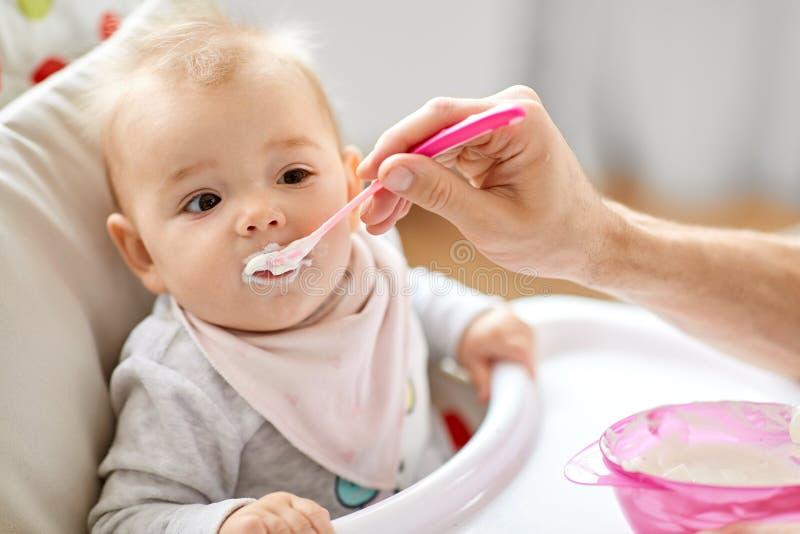 Bébé de alimentation de père s'asseyant dans le highchair à la maison images stock