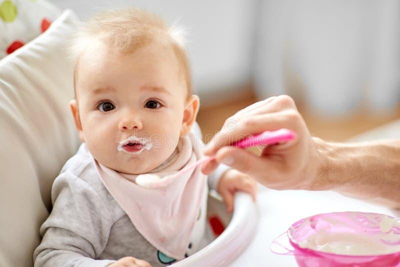 Bébé de alimentation de père s'asseyant dans le highchair à la maison photo stock