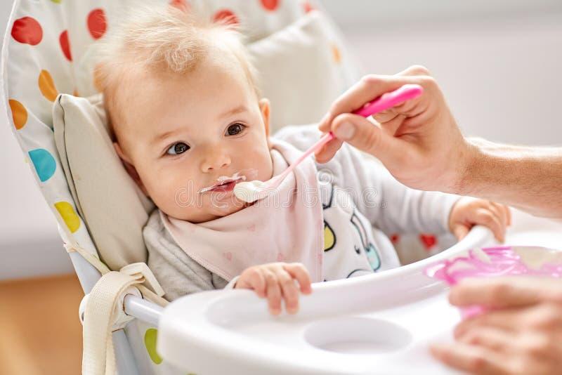 Bébé de alimentation de père s'asseyant dans le highchair à la maison photos libres de droits