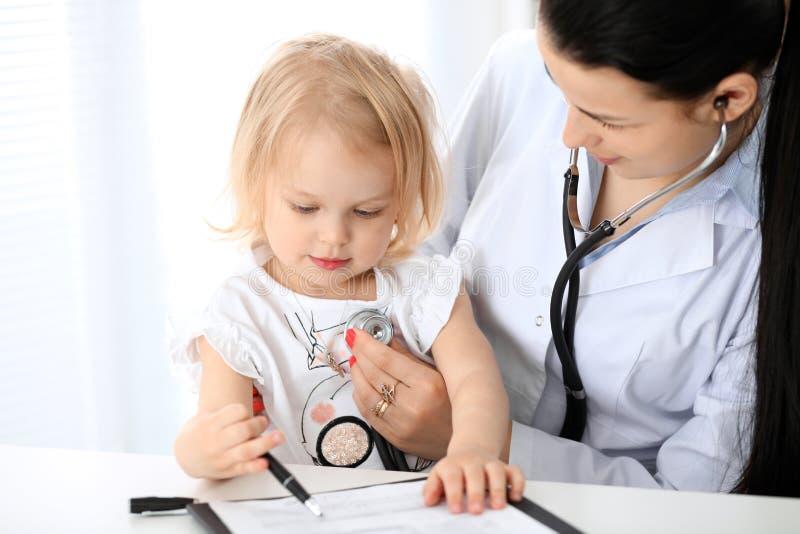 Bébé de docteur et de patient dans l'hôpital La petite fille est examinée par le pédiatre avec le stéthoscope Soins de santé photo stock