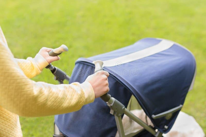Bébé de flânerie de mère dans le chariot en parc photo stock