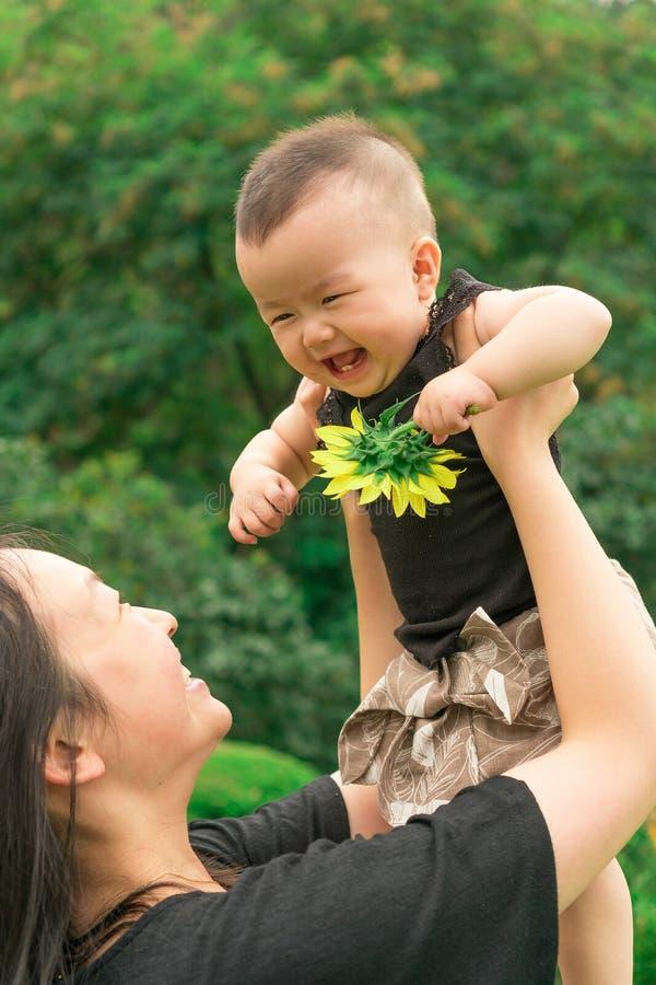 Bébé de levage de mère  photo stock