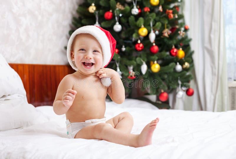Bébé de Noël dans le chapeau de Santa se reposant sur le lit image libre de droits