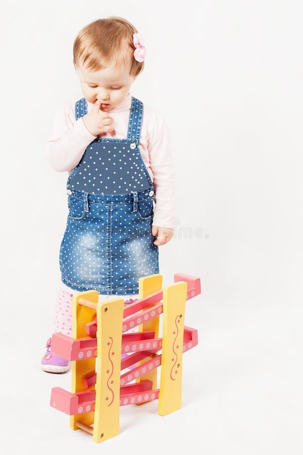 Bébé de pensée jouant avec le jeu de jouet pour le développement photo libre de droits