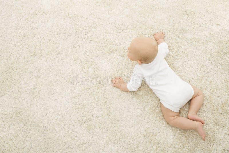Bébé de rampement sur le fond de tapis, vue supérieure d'enfant infantile, nouveau-née image stock