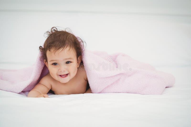 Bébé de sourire mignon se trouvant sous la couverture photographie stock libre de droits