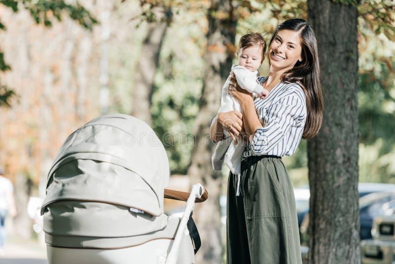 bébé de sourire de participation de mère près de poussette en parc et regard image libre de droits