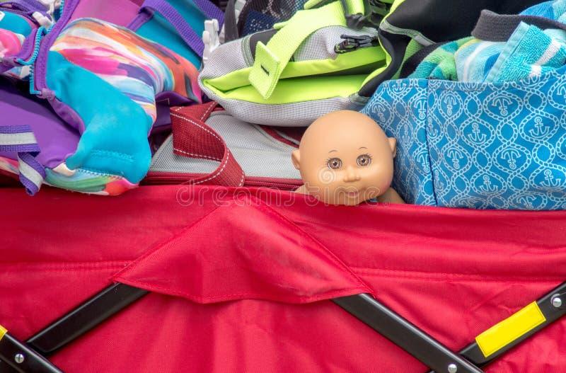 Bébé de sourire - poupée dans un chariot serré image libre de droits