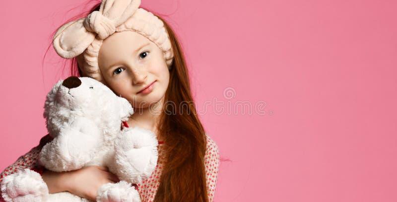 Bébé de sourire tenant un ours de nounours blanc dans la chambre un contexte rose photo stock