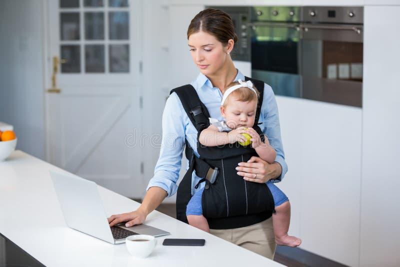 Bébé de transport de femme tout en à l'aide de l'ordinateur portable à la table photos libres de droits