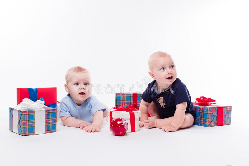 Bébé deux mignon s'asseyant sur le fond blanc parmi le Ba de Noël images libres de droits