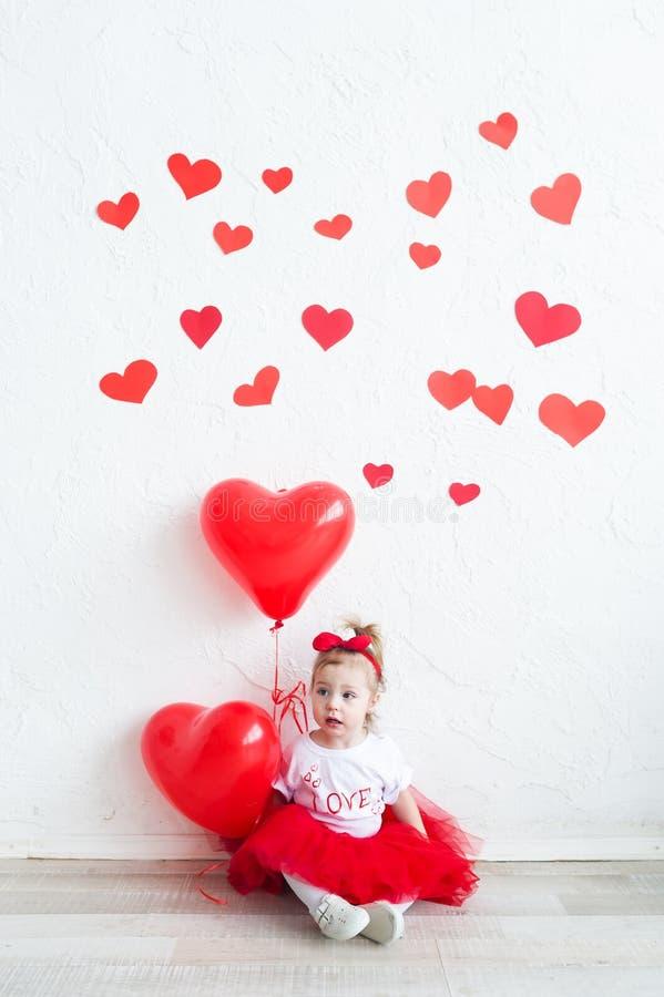 Bébé doux avec le coeur rouge Petite fille heureuse avec le ballon rouge à un mur de briques vide images libres de droits