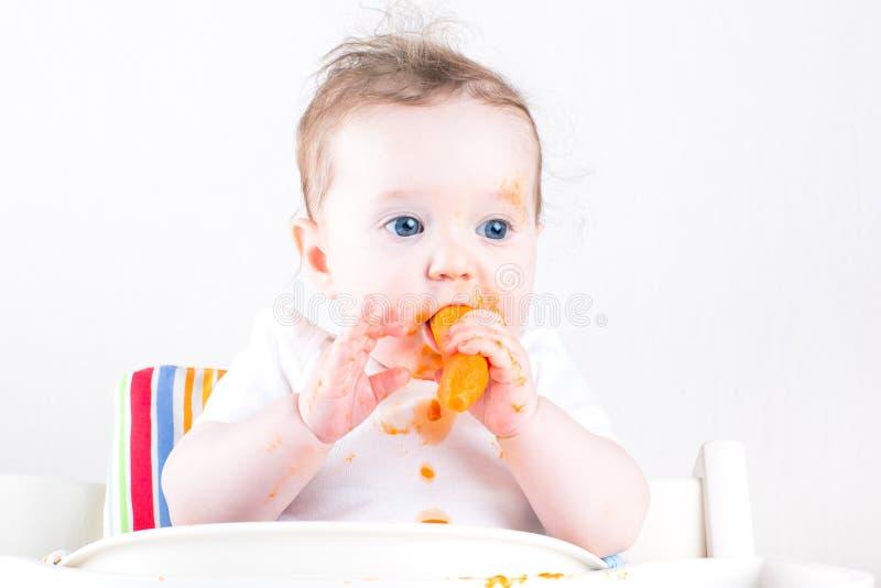 Bébé doux mangeant une carotte dans une chaise d'arbitre blanche photographie stock