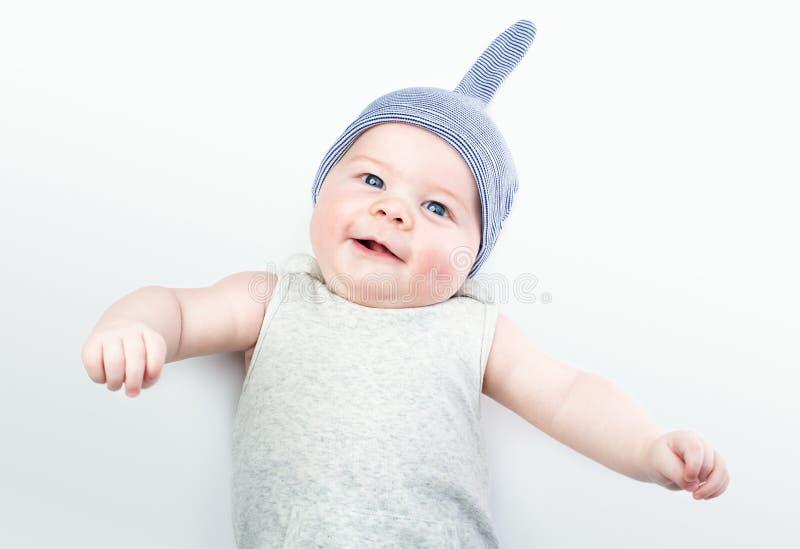 Bébé drôle dans un chapeau sur un fond clair Un petit garçon beau avec des yeux bleus image stock