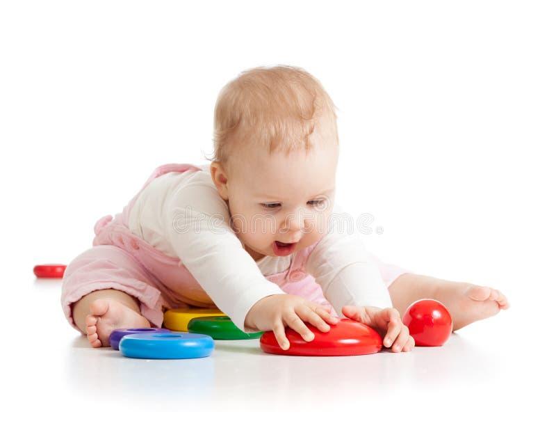 B?b? dr?le jouant avec le fond blanc d'ober d'isolement par jouets image stock