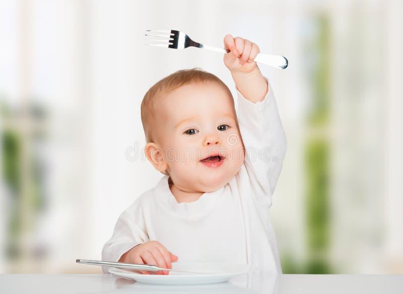 Bébé drôle avec un couteau et une fourchette mangeant de la nourriture photos libres de droits