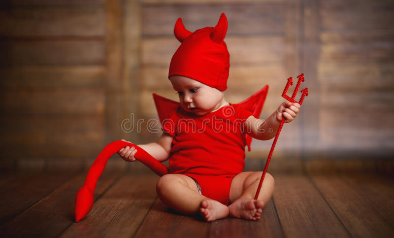 Bébé drôle dans le costume de Halloween de diable sur le fond en bois photo stock