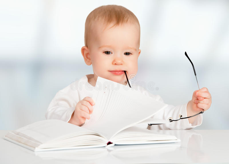 Bébé drôle lisant un livre photos stock