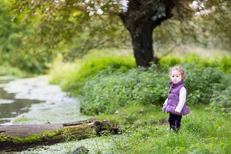 Bébé drôle mignon au rivage de rivière le jour froid photo libre de droits