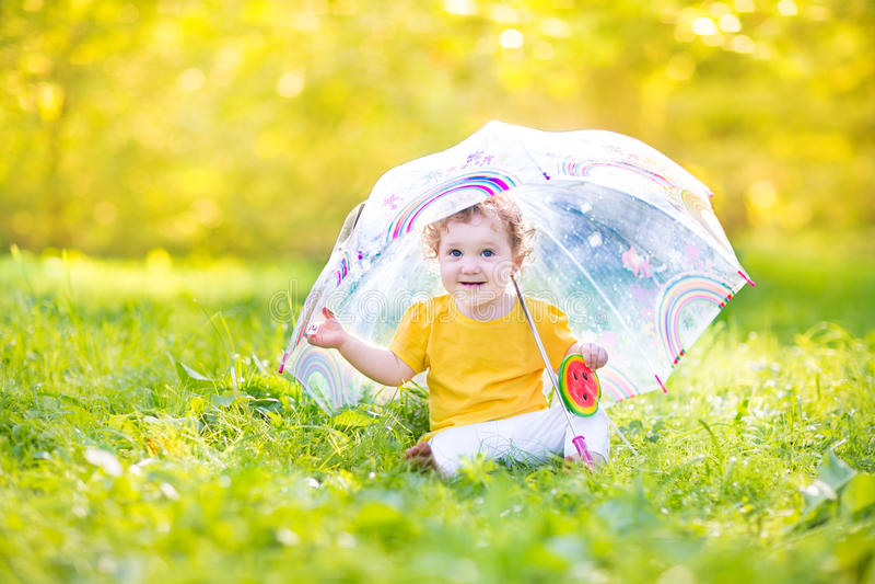 Bébé drôle mignon jouant sous la pluie sous le parapluie image libre de droits