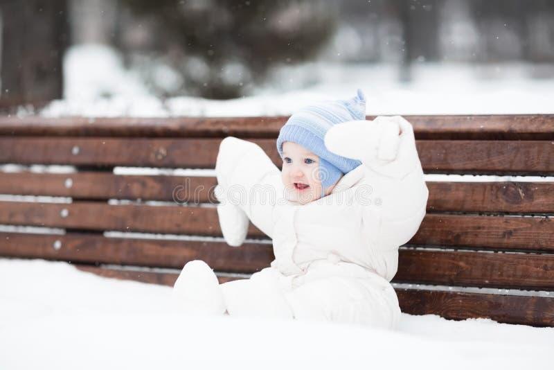 Bébé drôle mignon s'asseyant sur un banc en parc photos libres de droits