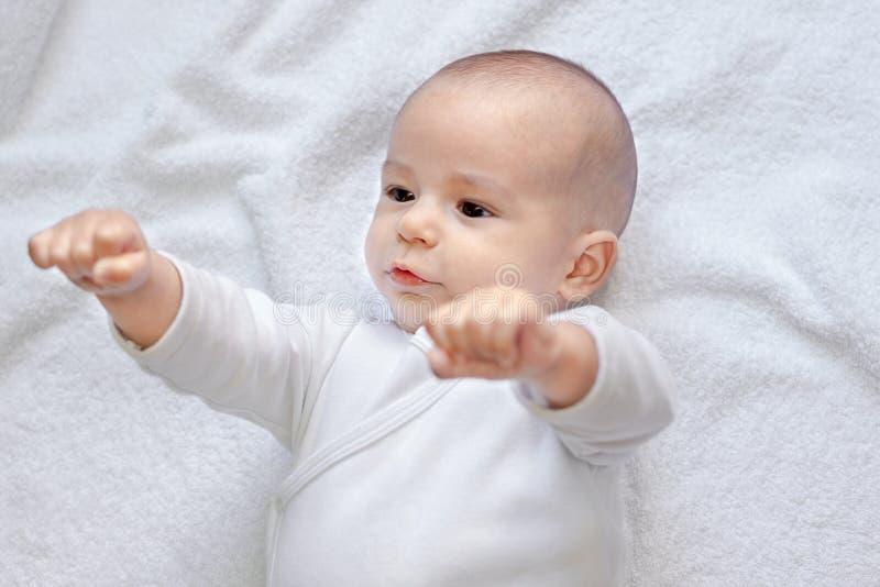 Bébé en bonne santé fort regardant des poings image stock