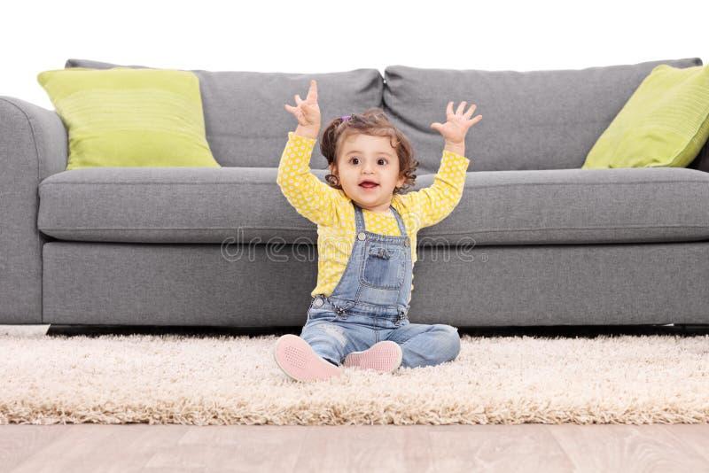 Bébé espiègle faisant des gestes le bonheur posé sur le plancher photos libres de droits
