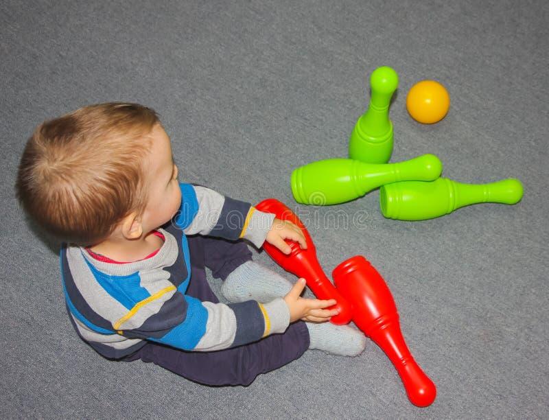 Bébé et bowling Un petit garçon s'assied sur le plancher avec le sketch photographie stock