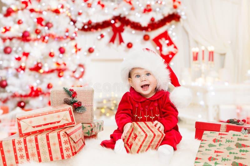 Bébé et Noël présentent des cadeaux, un petit enfant en chapeau rouge, un enfant heureux en salle de Noël photos stock
