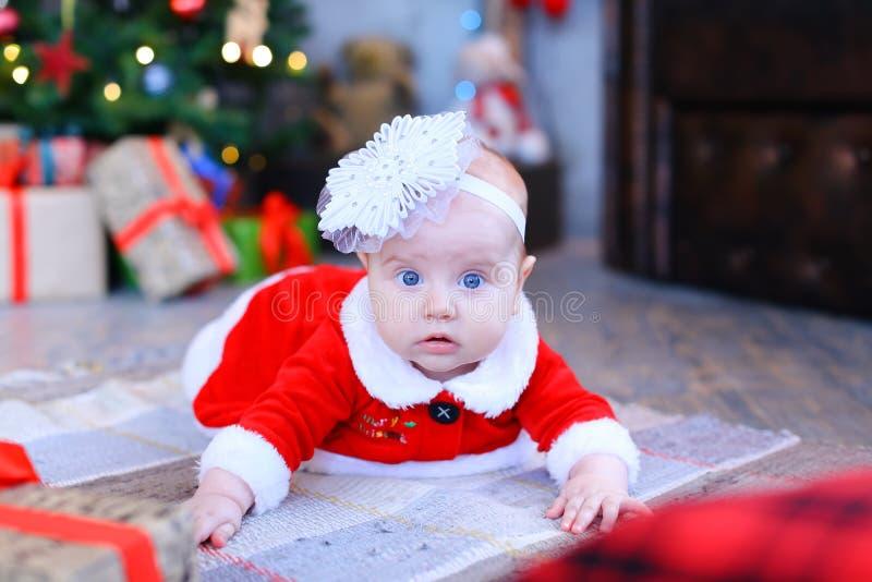 Bébé féminin se trouvant sur le plancher près de l'arbre et des présents de Noël image libre de droits