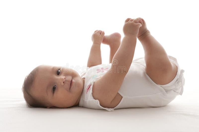 Bébé fier retenant ses pieds photos stock