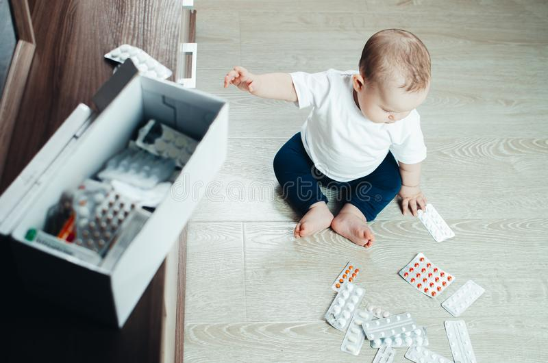 Bébé, fille s'asseyant sur le plancher dans les mains des pilules photo stock