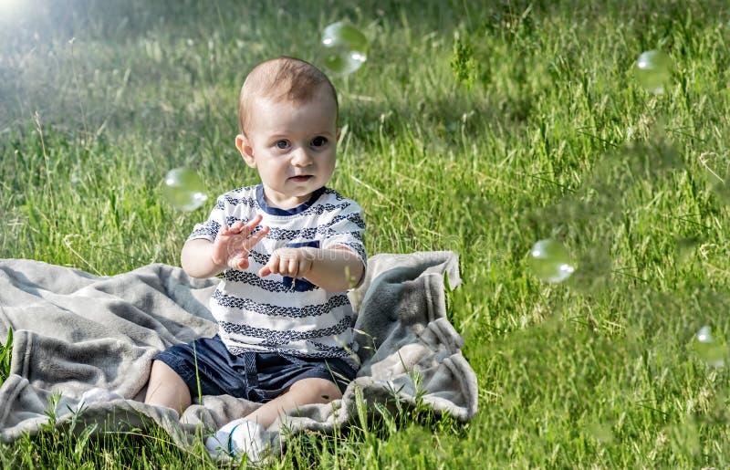 Bébé garçon étonné mignon whatching aux bulles et à la séance de savon de vol sur l'herbe verte au jour ensoleillé d'été image libre de droits