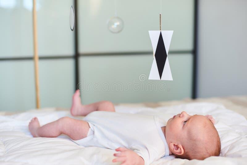 Bébé garçon adorable dans le mensonge et les regards ensoleillés blancs de chambre à coucher au mobile de Munari Montessori photo libre de droits